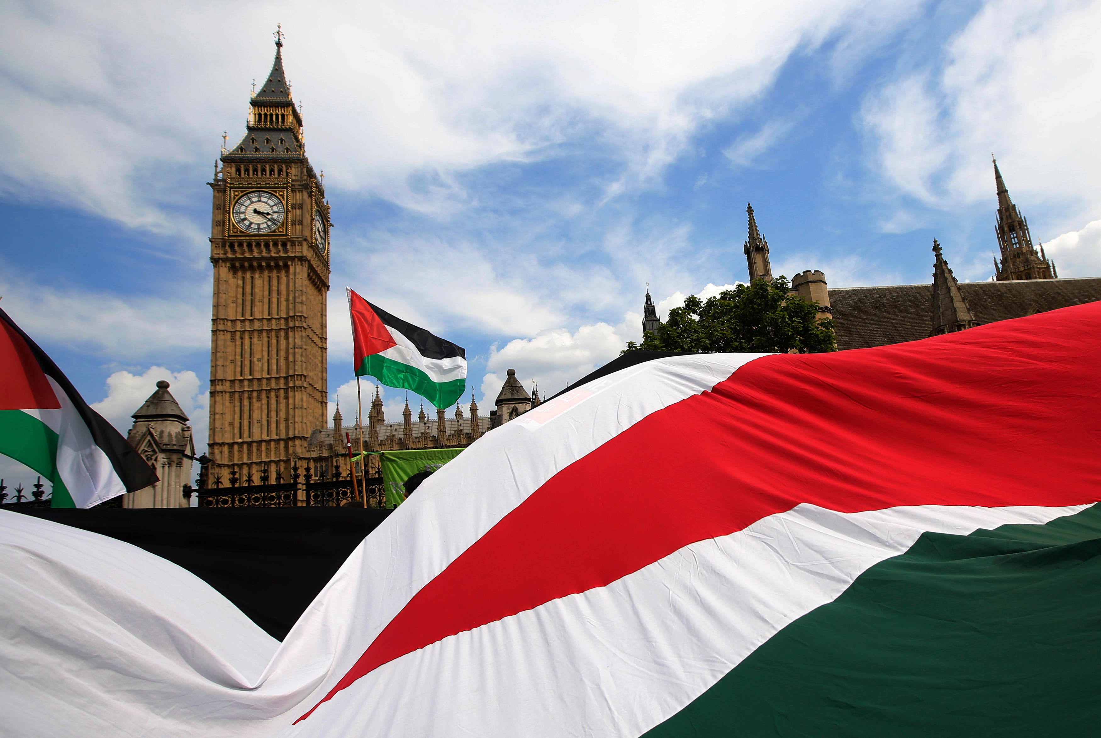 Demonstrators carry Palestinian flags as they protest outside the Houses of Parliament in central London July 26, 2014. (Reuters)