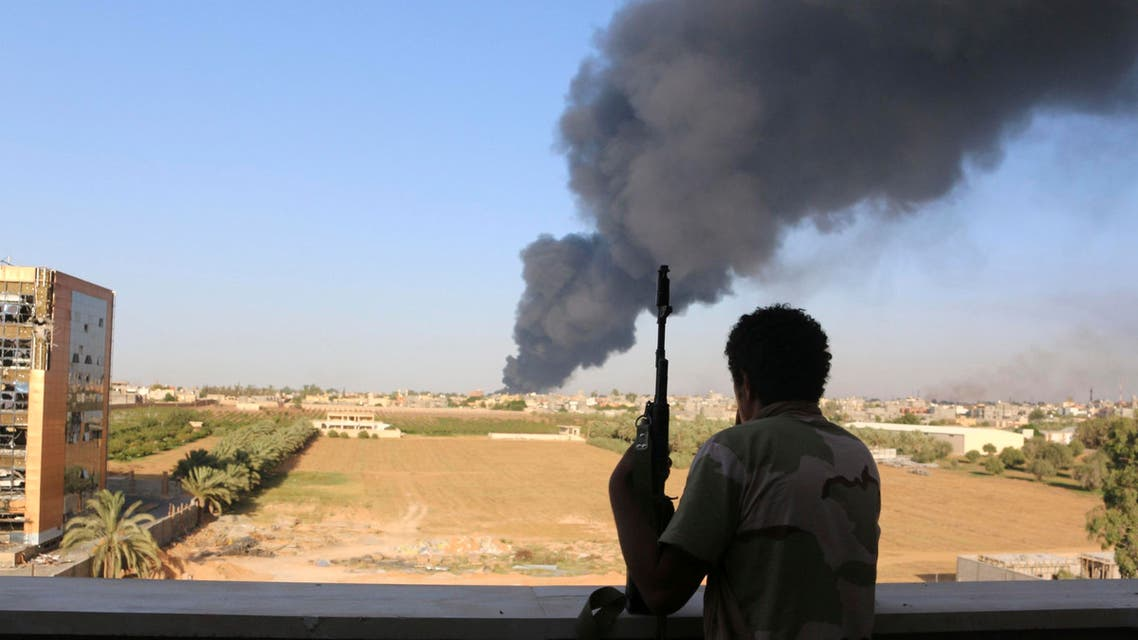 A fighter from Zintan brigade watches as smoke rises after rockets fired by one of Libya's militias struck and ignited a fuel tank in Tripoli August 2, 2014. (Reuters)