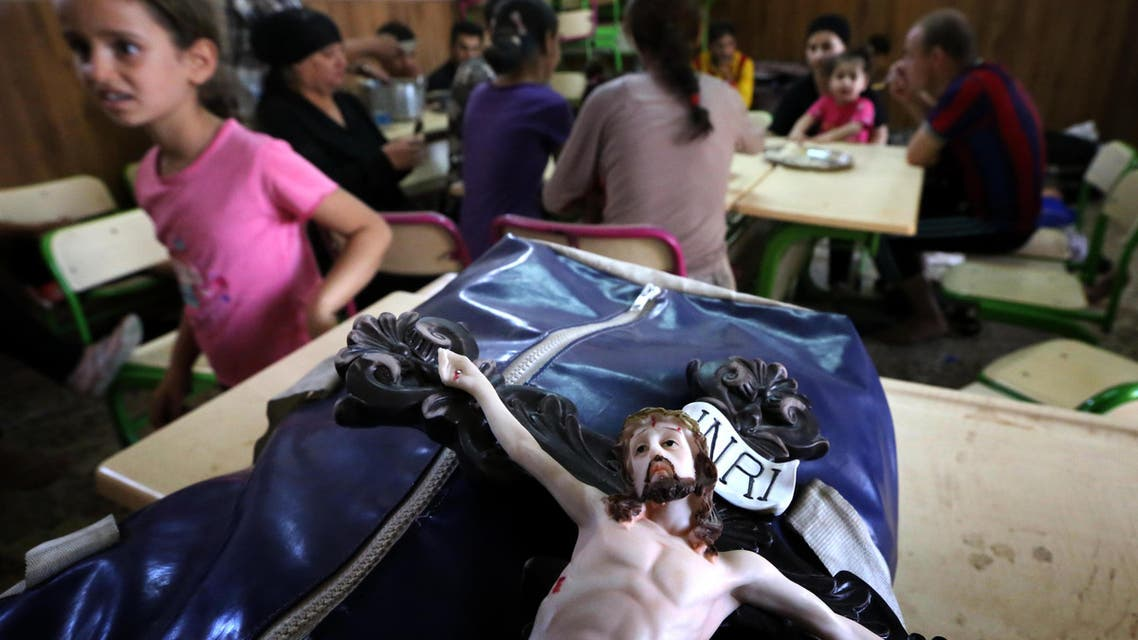 A statue of Jesus Christ is seen on the bag of an Iraqi Christian who fled the violence in the village of Qaraqush. AFP