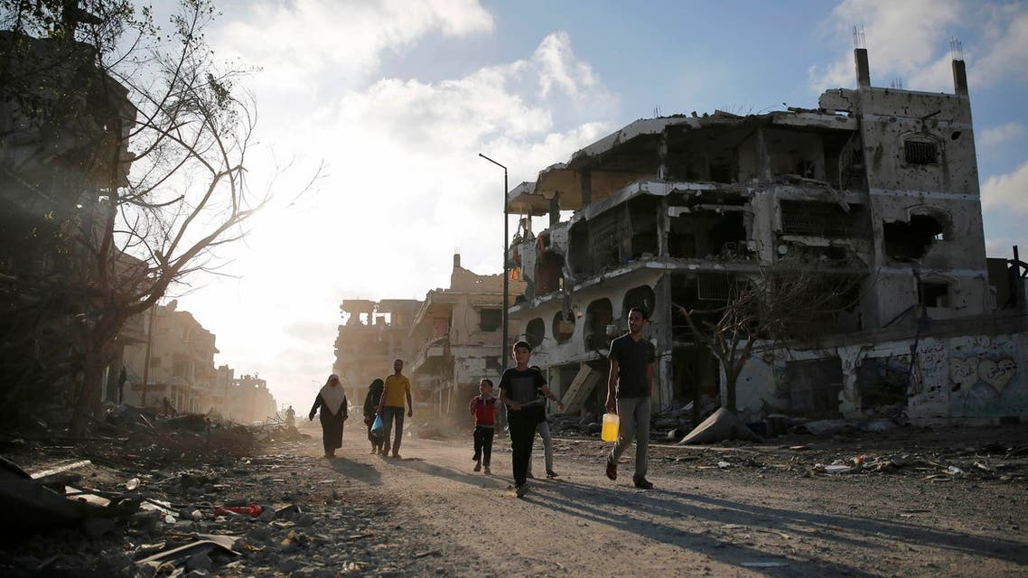 Palestinians walk amid the ruins of destroyed homes in the Shejaia neighbourhood, which witnesses said was heavily hit by Israeli shelling and air strikes during an Israeli offensive, in Gaza City August 6, 2014.