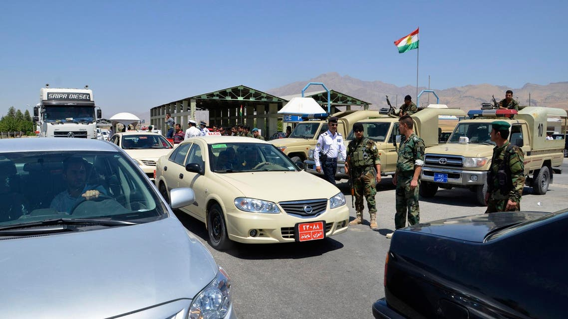 """Kurdish """"peshmerga"""" troops stand guard during an intensive security deployment at the checkpoint at the entrance to Sulaimaniya province August 8, 2014."""