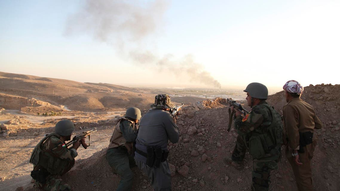 Iraqi Kurdish Peshmerga troops watch as smoke billows from the town of Makhmur during clashes with ISIS militants August 9, 2014. (Reuters)