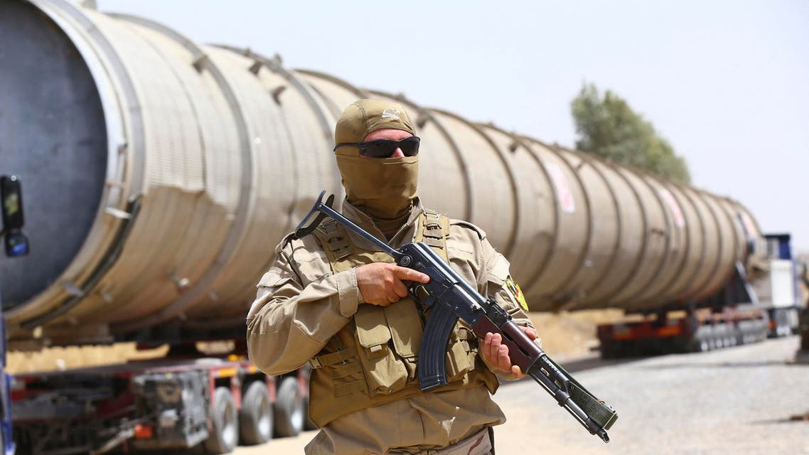 A member of the Kurdish security forces takes up position with his weapon as he guards a section of an oil refinery, which is being brought on a truck to Kalak refinery in the outskirts of Arbil, in Iraq's Kurdistan region, July 14, 2014. (Reuters)