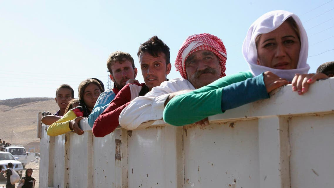 Displaced people from the minority Yazidi sect, fleeing the violence in the Iraqi town of Sinjar, re-enter Iraq from Syria at the Iraqi-Syrian border crossing in Fishkhabour, Dohuk Province, August 10, 2014. Reuters
