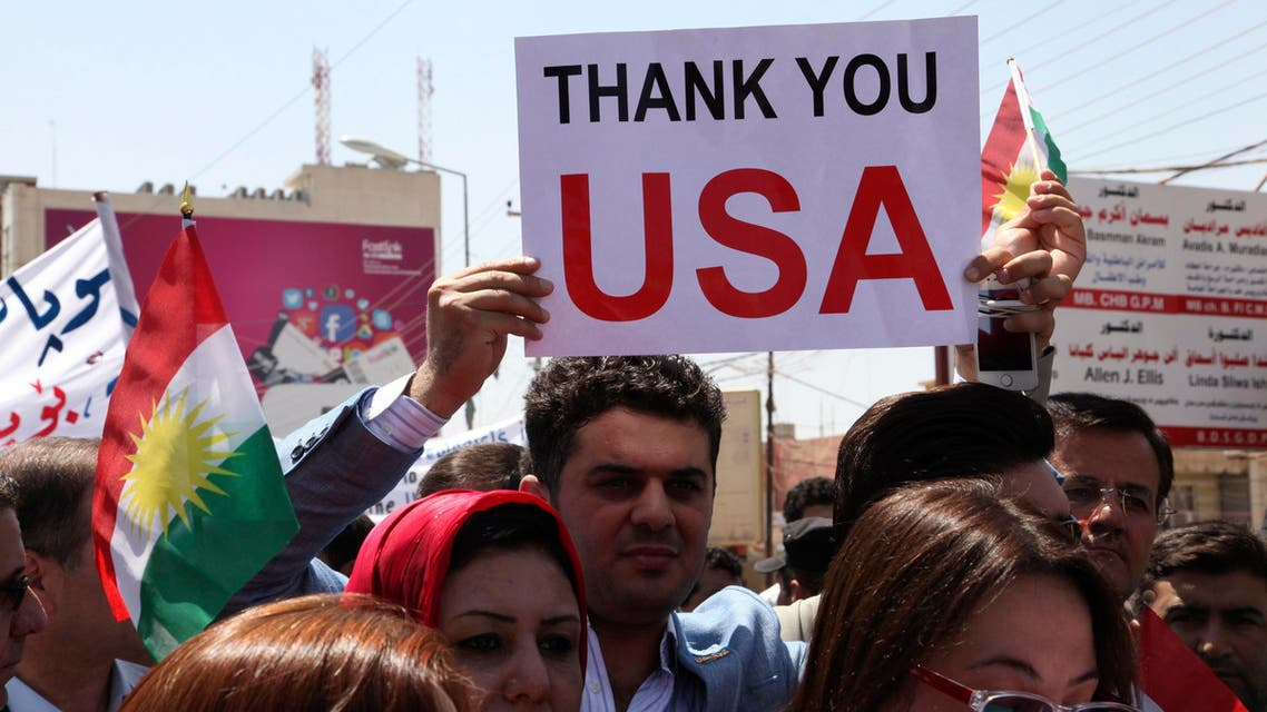A Kurdish resident holds a signs during a demonstration in support of the Peshmerga troops in front of the U.S. consulate in Arbil, north of Baghdad, August 11, 2014.