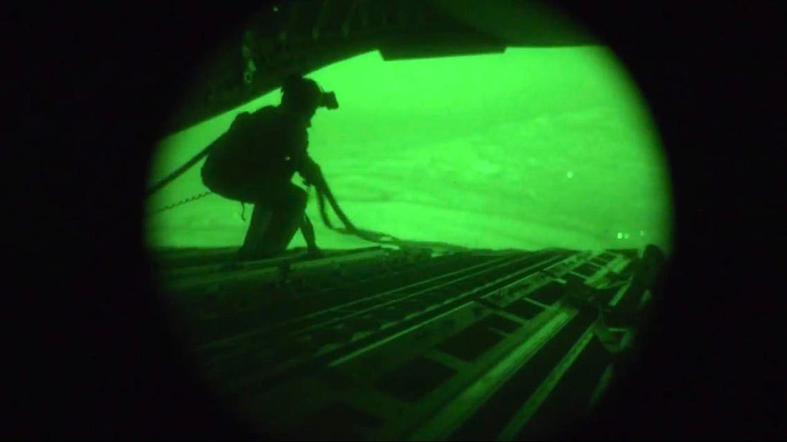 A still image captured from the U.S. Central Command night vision video footage shows an Air Force personnel retrieving straps after the U.S. military airdrop of food and water for thousands of Iraqi citizens threatened by the ISIS near Sinjar, Iraq on August 9, 2014. (Reuters)