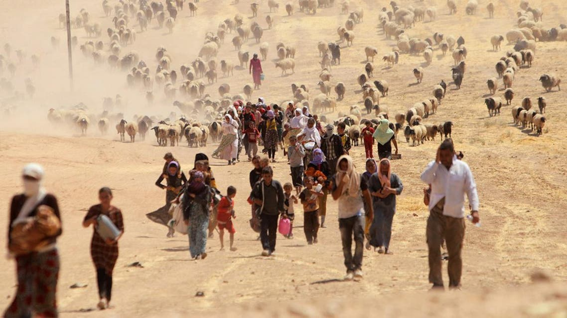 Displaced people from the minority Yazidi sect, fleeing the Islamic State in Sinjar, ride on a truck towards the Syrian border. (Reuters)