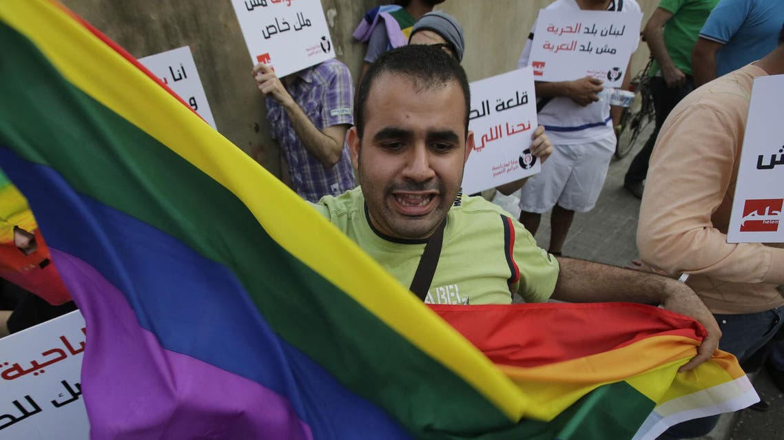 A protester waves a gay pride flag as others hold banners during an anti-homophobia rally in Beirut on April 30, 2013. (AFP)