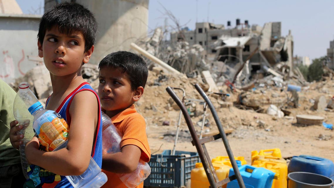 Palestinian children wait to collect water during a five-day truce in Khan Younis in the southern Gaza Strip August 14, 2014.