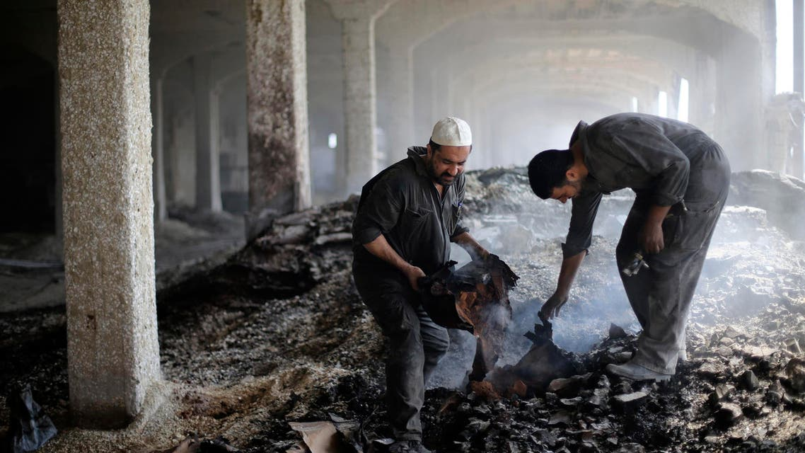 Palestinian workers gather debris inside al-Awdah food factory, which witnesses said was shelled and torched by the Israeli army during the offensive, in Deirl al-Balah in the central Gaza Strip August 14, 2014. (Reuters)