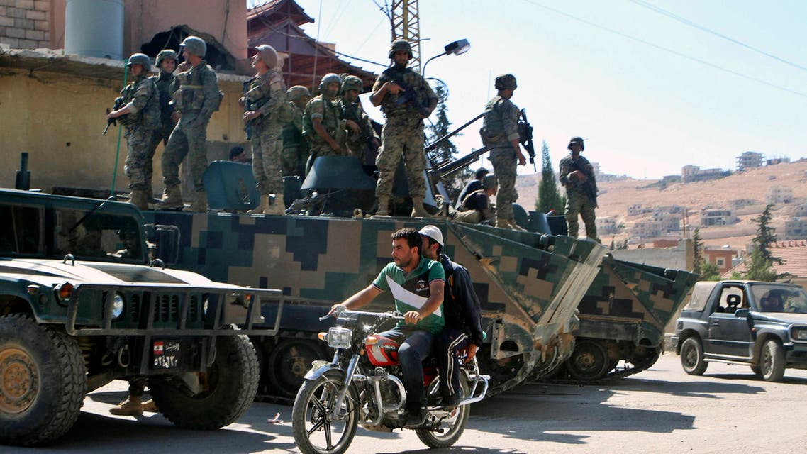 Men ride a motorcycle past Lebanese Army soldiers on armoured carriers at the Sunni Muslim border town of Arsal, in eastern Bekaa Valley August 9, 2014. (Reuters)