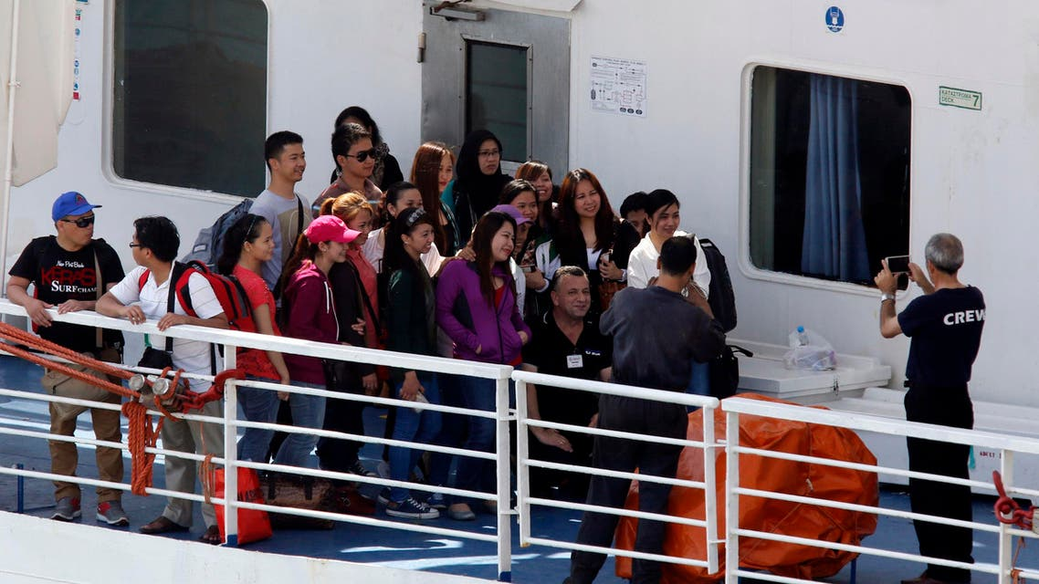 Filipino nationals pose for photos with a crew member on the deck of the MV Bridge after it arrived from Libya in Valletta's Grand Harbour August 15, 2014.