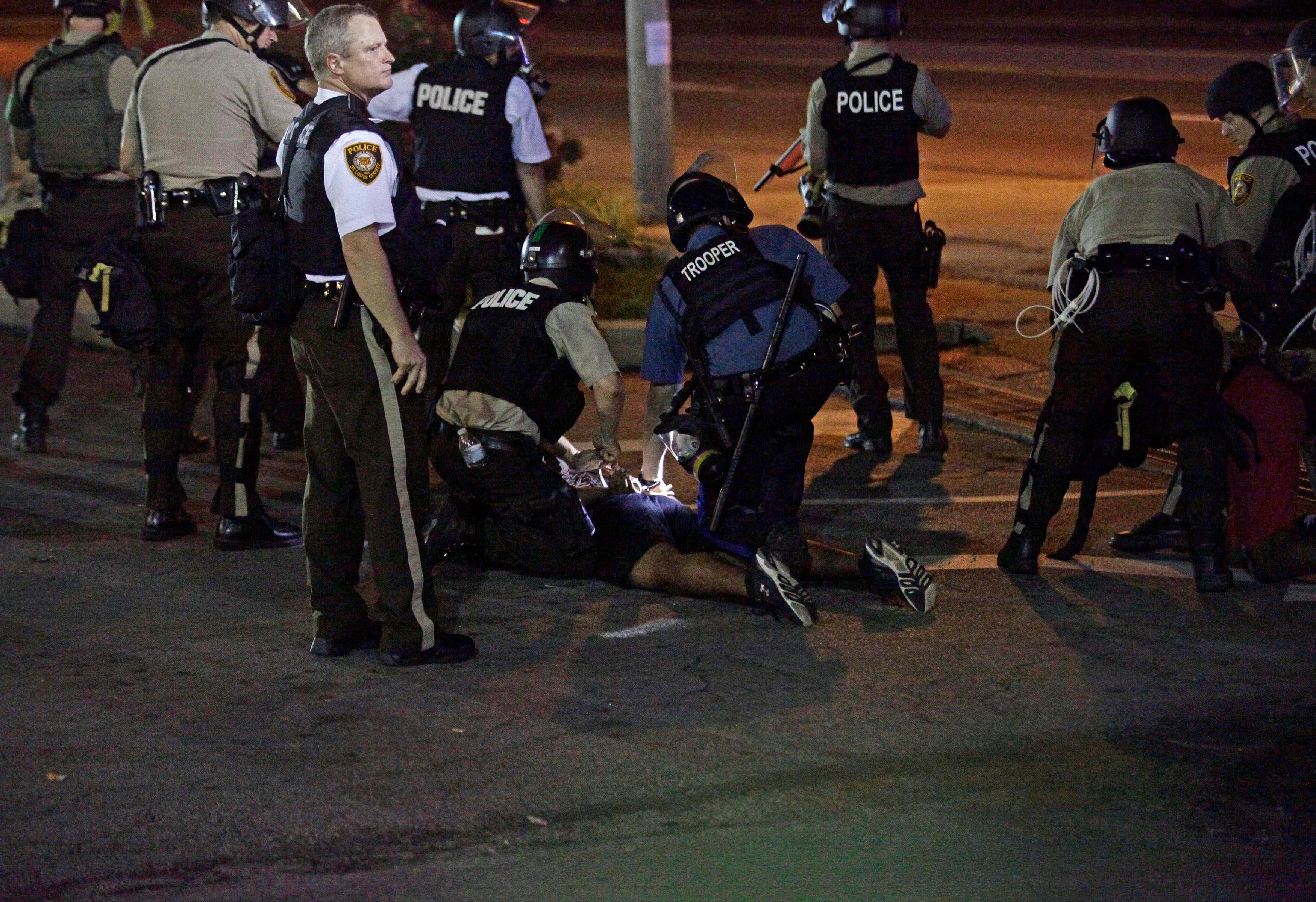Police detain a demonstrator during a protest against the shooting death of Michael Brown in Ferguson Missouri August 18, 2014.Reuters