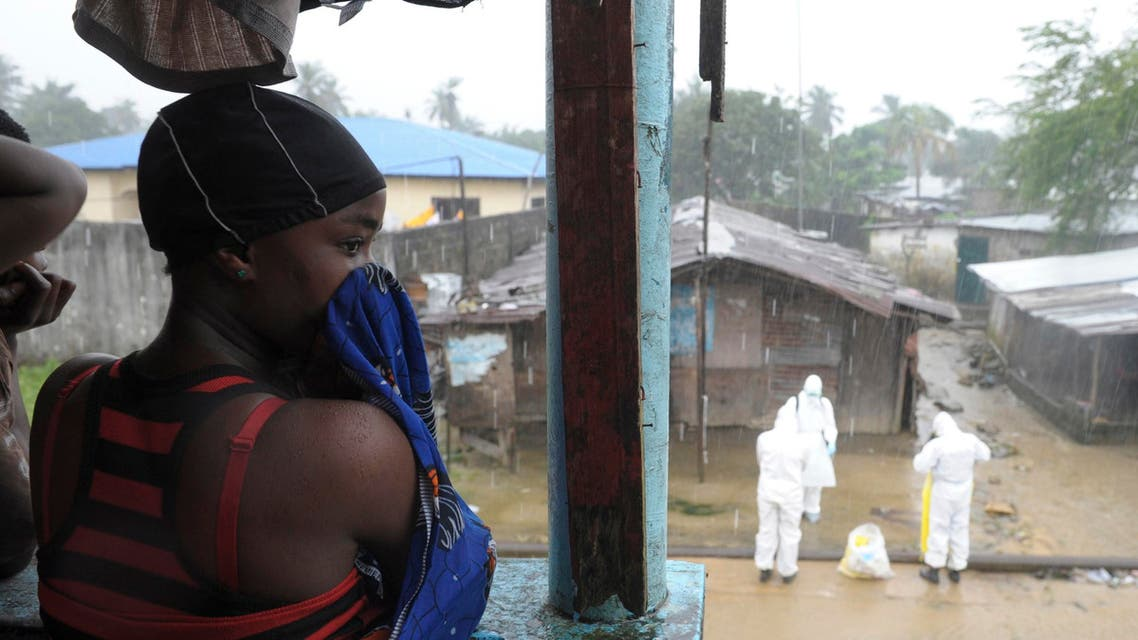 A Liberian woman stands as health workers wearing protective clothing prepare to carry an abandoned dead body presenting with Ebola symptoms at Duwala market in Monrovia August 17, 2014. (Reuters)