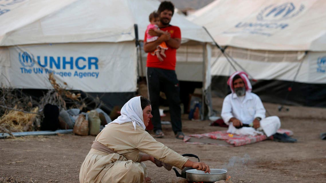Displaced people from the minority Yazidi sect, who fled the violence in the Iraqi town of Sinjar, sit on the ground at Bajed Kadal refugee camp south west of Dohuk province August 15, 2014. (Reuters)