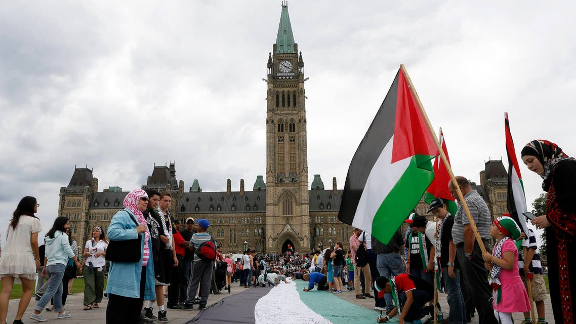 Pro-Palestinian protesters sign a giant Palestinian flag during a demonstration against Israel's military action in the Gaza Strip, on Parliament Hill in Ottawa July 26, 2014. (Reuters)