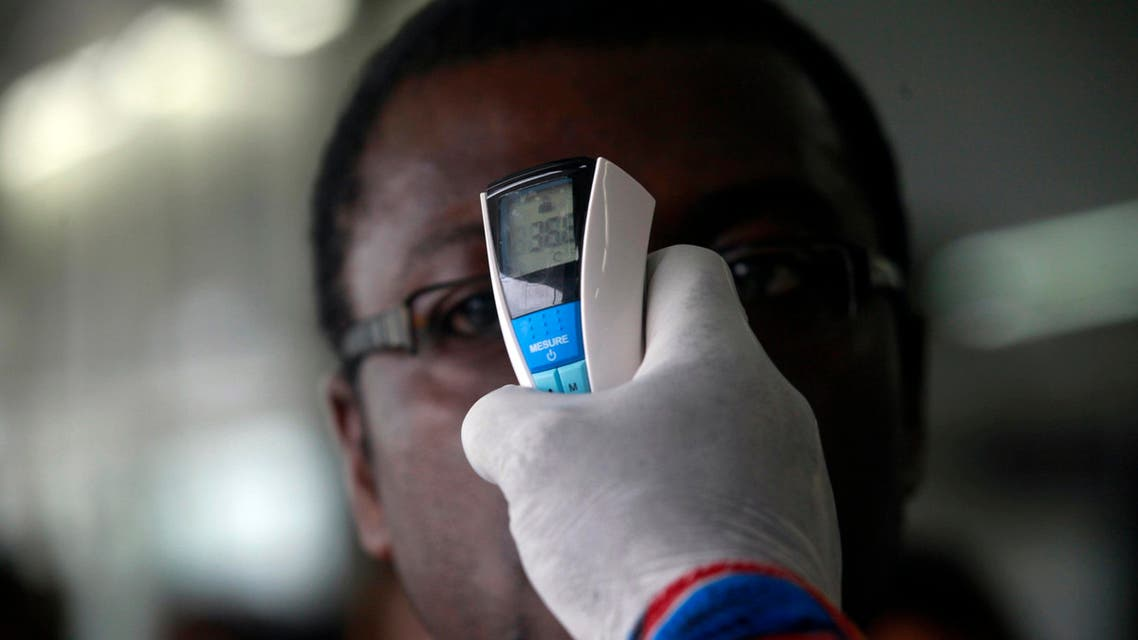 A health worker takes a passenger's temperature with an infrared digital laser thermometer at the Felix Houphouet Boigny international airport in Abidjan August 13, 2014. (Reuters)