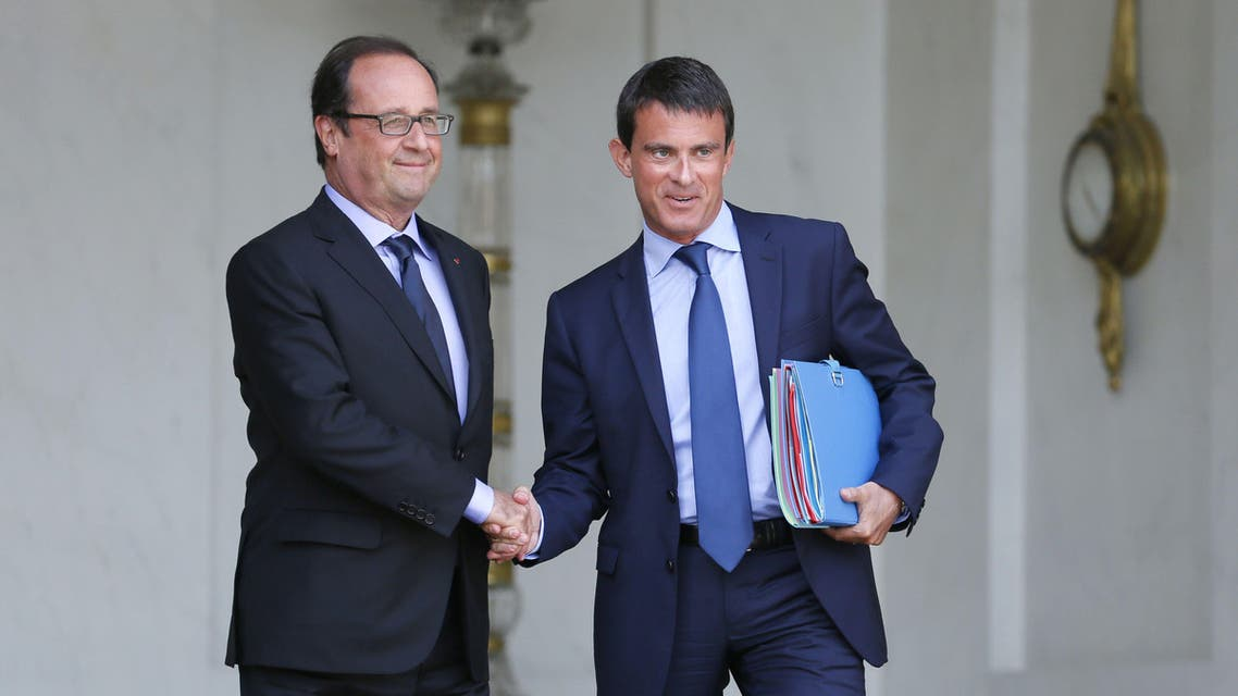 French President Francois Hollande (L) and French Prime Minister Manuel Valls shaking hands at the Elysee presidential palace. (AFP)