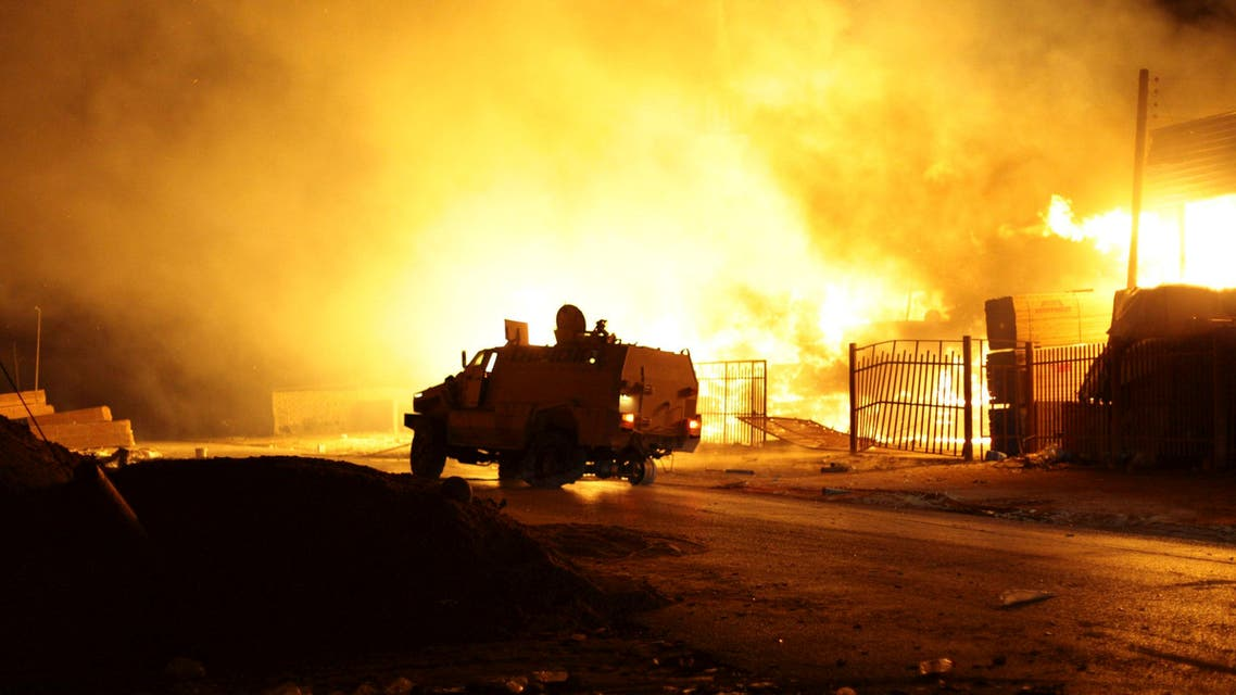A building on fire, which witnesses say was hit by a rocket, burns after clashes between rival militias in the Sarraj district in Tripoli August 23, 2014. reuters