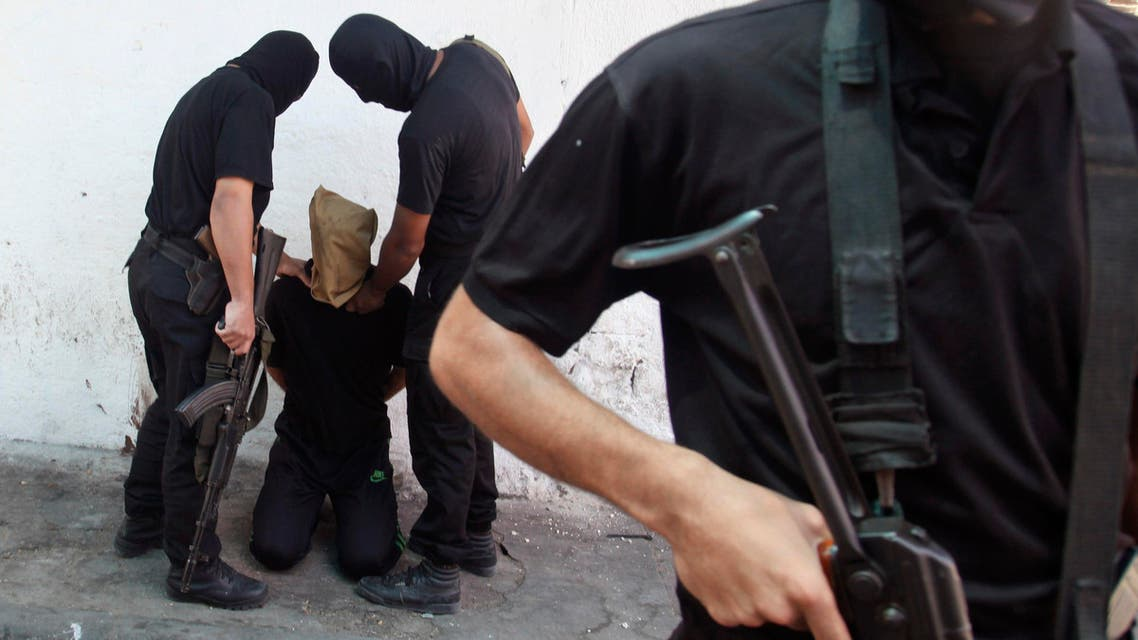 Hamas militants grab a Palestinian suspected of collaborating with Israel before being executed in Gaza City August 22, 2014. (Reuters)