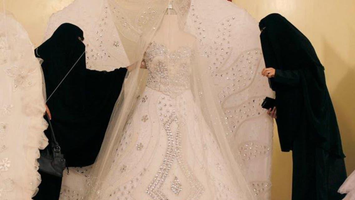 Women in Burkas screening a wedding dress (File photo: Reuters)