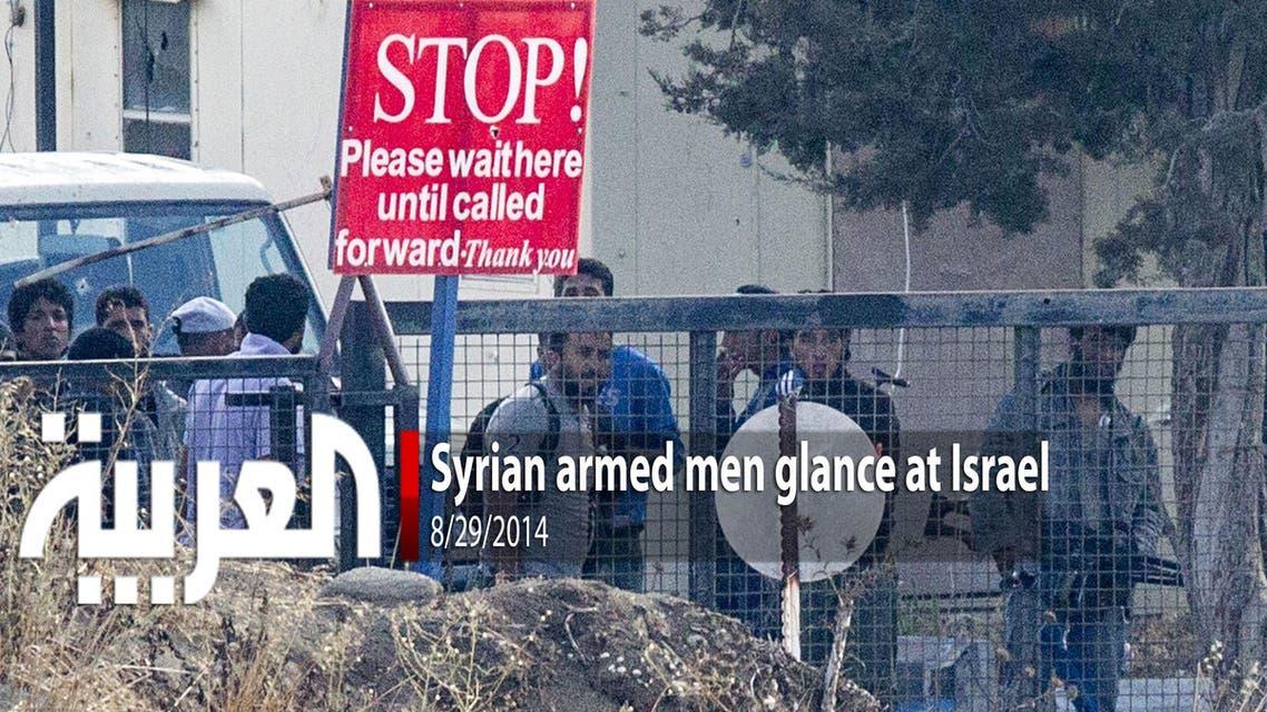 Syrian armed men glance at Israel