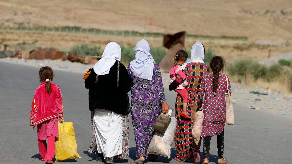 Women and children from the minority Yazidi sect, fleeing the violence in the Iraqi town of Sinjar, walk to a refugee camp after they re-entered Iraq from Syria at the Iraqi-Syrian border crossing in Fishkhabour, Dohuk province, August 14, 2014. reuters