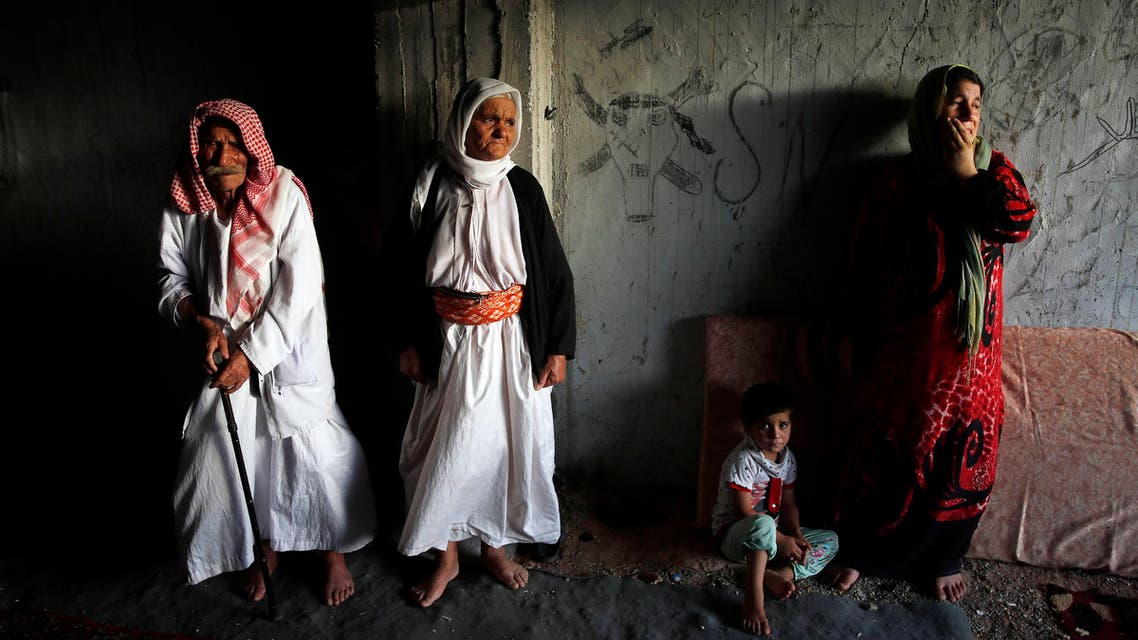 Displaced people from the minority Yazidi sect who fled the violence in the Iraqi town of Sinjar, wait for aid at an abandoned building that they are using as their main residence, outside the city of Dohuk August 25, 2014. (Reuters)
