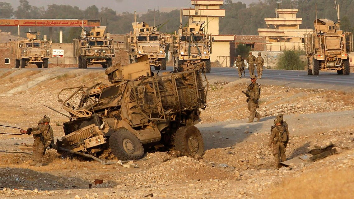 U.S. troops assess the damage to an armoured vehicle of NATO-led International Security Assistance force (ISAF) at the site of a suicide attack in Jalalabad province, August 24, 2014. (Reuters)