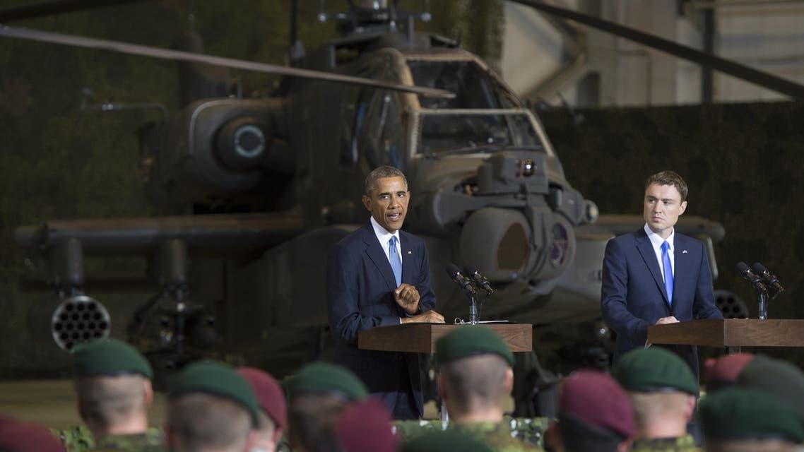 S President Barack Obama (L) speaks next to Prime Minister Taavi Roivas of Estonia to US and Estonian members of the military at a hangar at Tallinn Airport in Tallinn, Estonia, September 3, 2014.