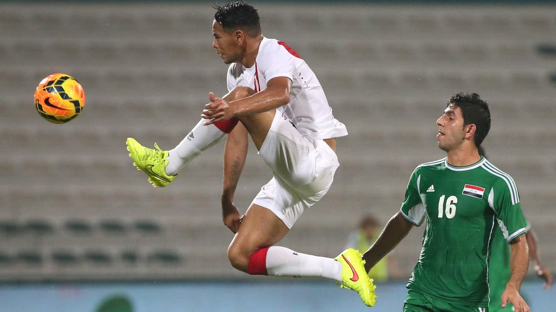 Iraqi's Mohanad Abdul Raheem (L) vies with Alexander Callens (R) of Peru during their friendly football match in Dubai on September 4, 2014. (AFP)