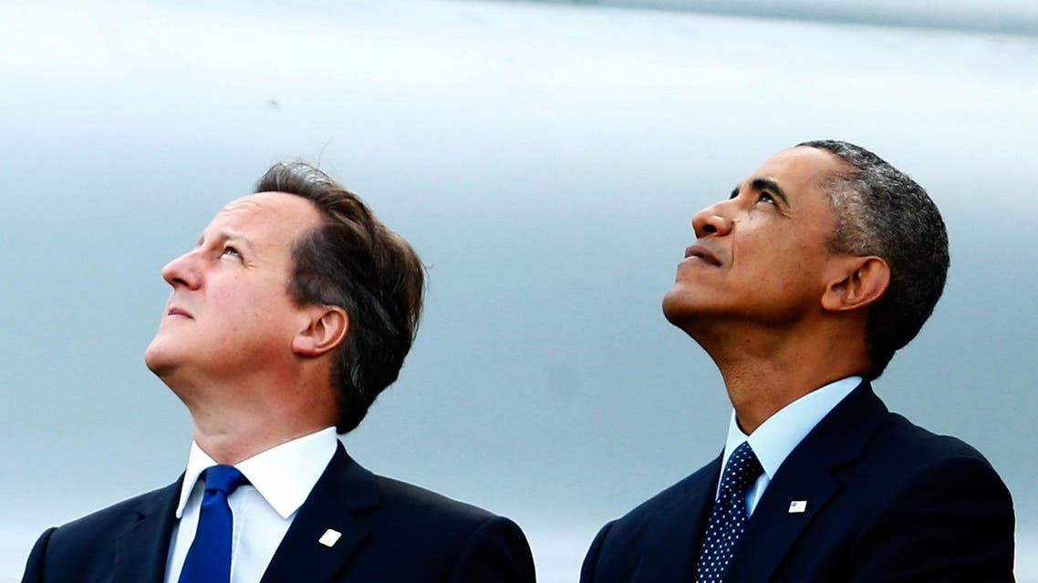 Britain's Prime Minister David Cameron (L) and U.S. President Barack Obama watch a fly-past by the Red Arrows during the NATO summit