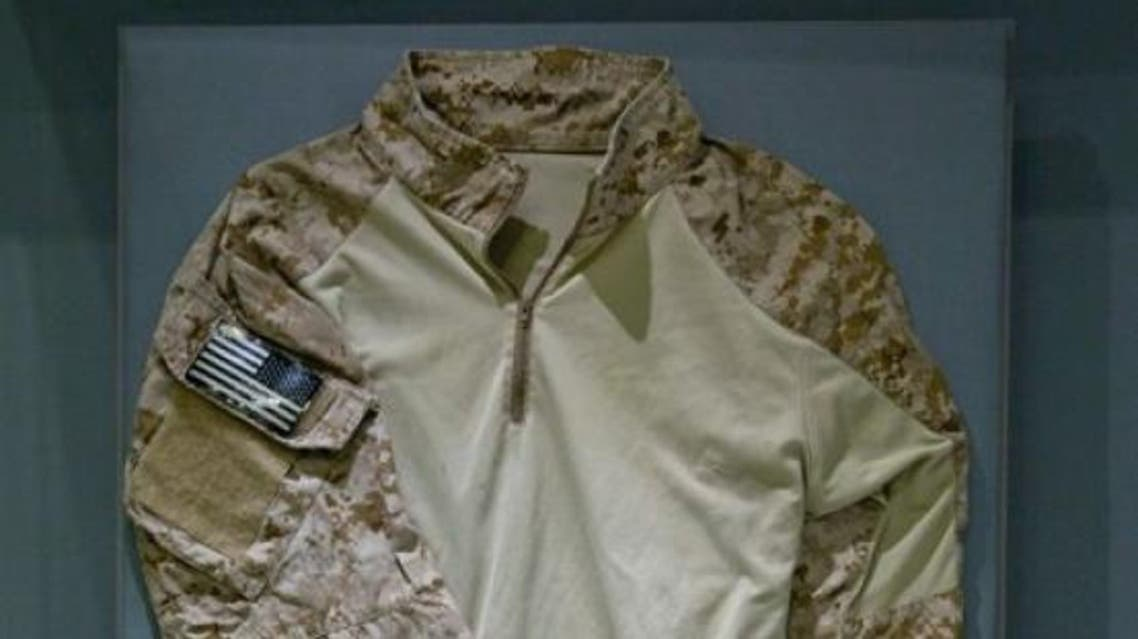 The uniform shirt, tan with camouflage sleeves and an American flag patch belonged to a now-retired member of SEAL Team Six. (Photo courtesy: AP)