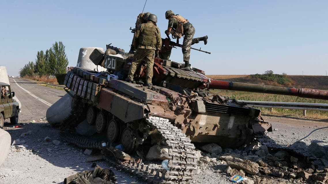 Ukrainian soldiers inspect a damaged tank on the outskirts of the southern coastal town of Mariupol, September 6, 2014. d