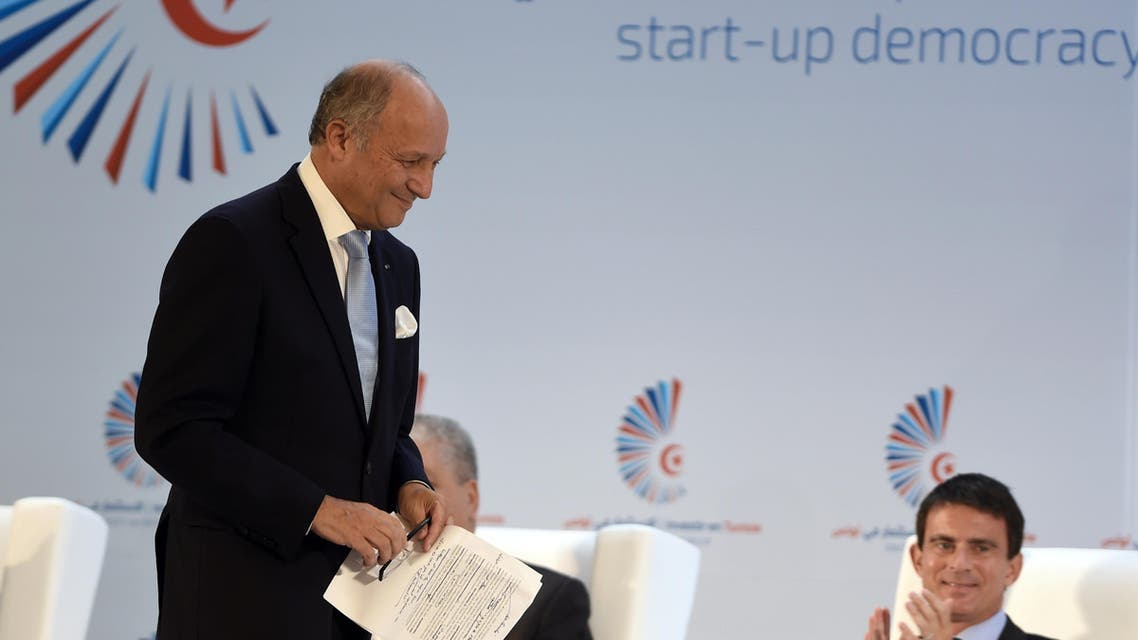 """French Foreign Minister Laurent Fabius and Prime Minister Manuel Valls (R) attend the opening session of the """"Invest in Tunisia, Start-up Democracy."""" (AFP)"""