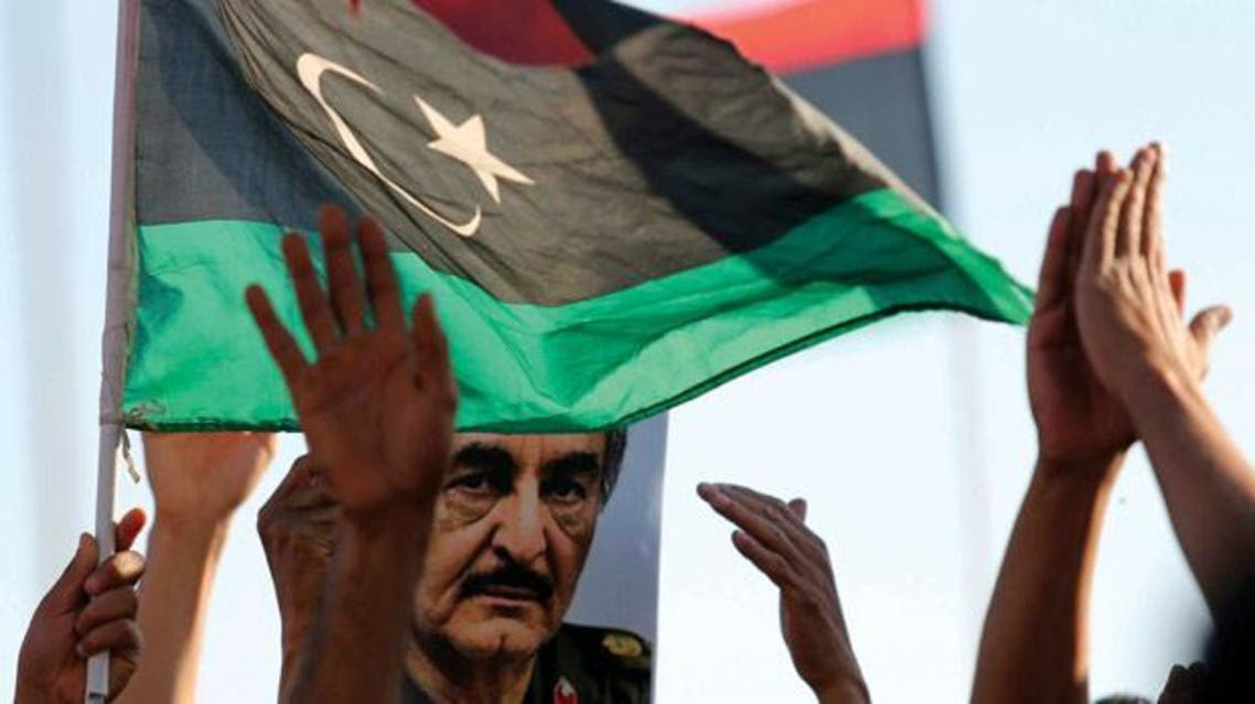 A picture of General Khalifa Haftar is seen next to a Libyan flag during a demonstration in Benghazi. Photo: Esam Omran Al-Fetori/Reuters