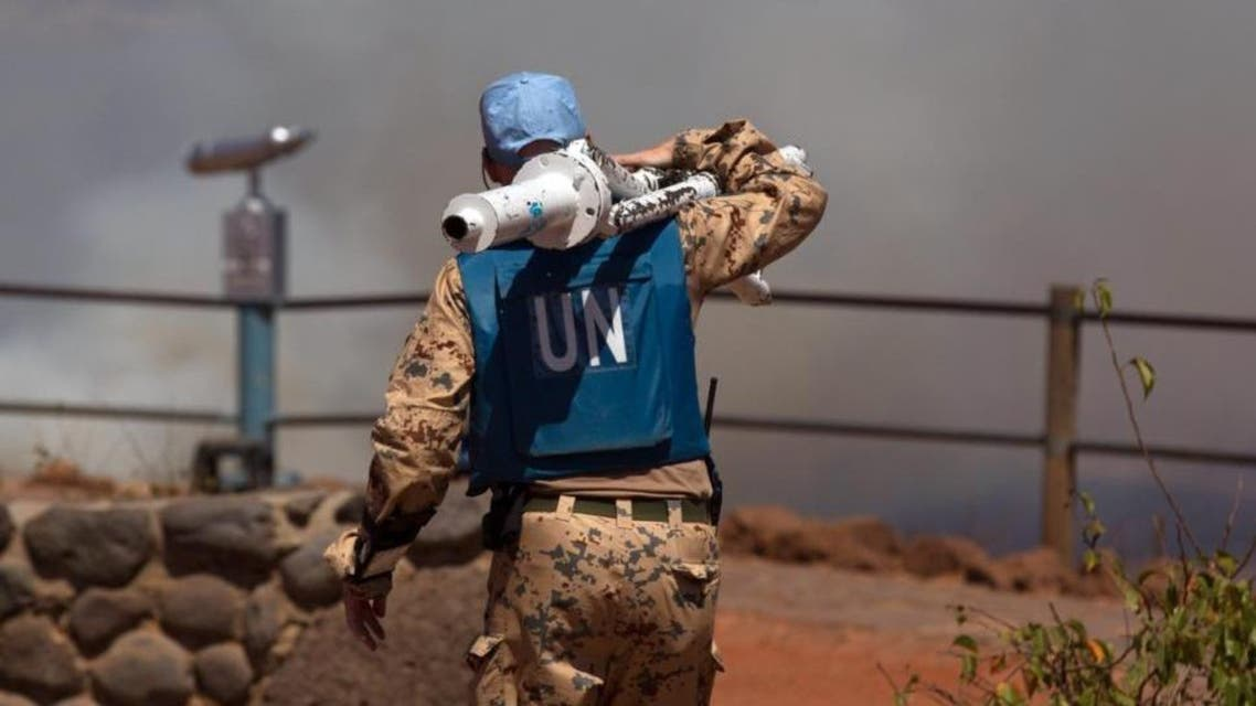 A UN peacekeeper carries equipment at the Syrian-Israeli border.
