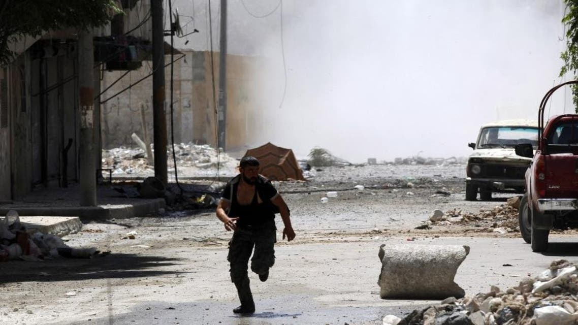 A man runs for cover during clashes between Free Syrian Army fighters and Syrian Army soldiers in the Salah al-Din neighborhood of central Aleppo. (Reuters)