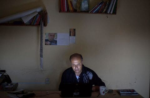 Palestinian painter Basel al-Maqosui, 42, works on a collage on his computer in his office in Gaza City, Sept. 7, 2014. (Photo courtesy: AP)