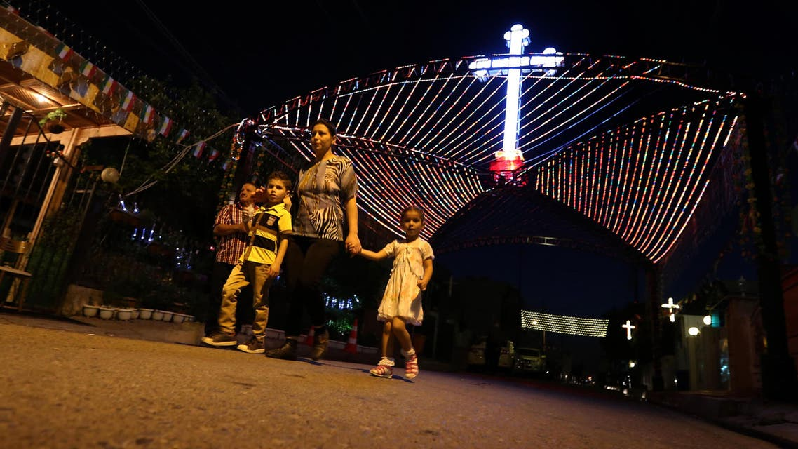 Some Iraqi Christians fled to other cities in Iraq, such as Mosul.  Iraqi Christians walk past a decorations displayed in commemoration of the Elevation of the Holy Cross festival in Erbil, the capital of the Kurdish autonomous region in northern Iraq, Sept. 15, 2014. (AFP)