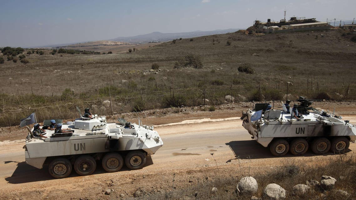 United Nations Disengagement Observer Force (UNDOF) armoured personnel carriers, including an armed one (R), escort a convoy of UNDOF vehicles leaving the Syrian side of the Golan Heights, on September 15, 2014. (AFP)