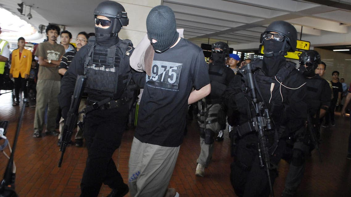 Elite Indonesian anti-terror police from Densus 88 escort four Turks arrested on arrival at Jakarta airport on September 14, 2014. (AFP)