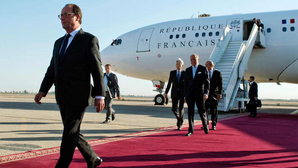 French President Francois Hollande (L), French Foreign minister Laurent Fabius (C) and French Defence minister Jean-Yves Le Drian (Rear) exit their plane after landing at Baghdad airport September 12, 2014. reuters