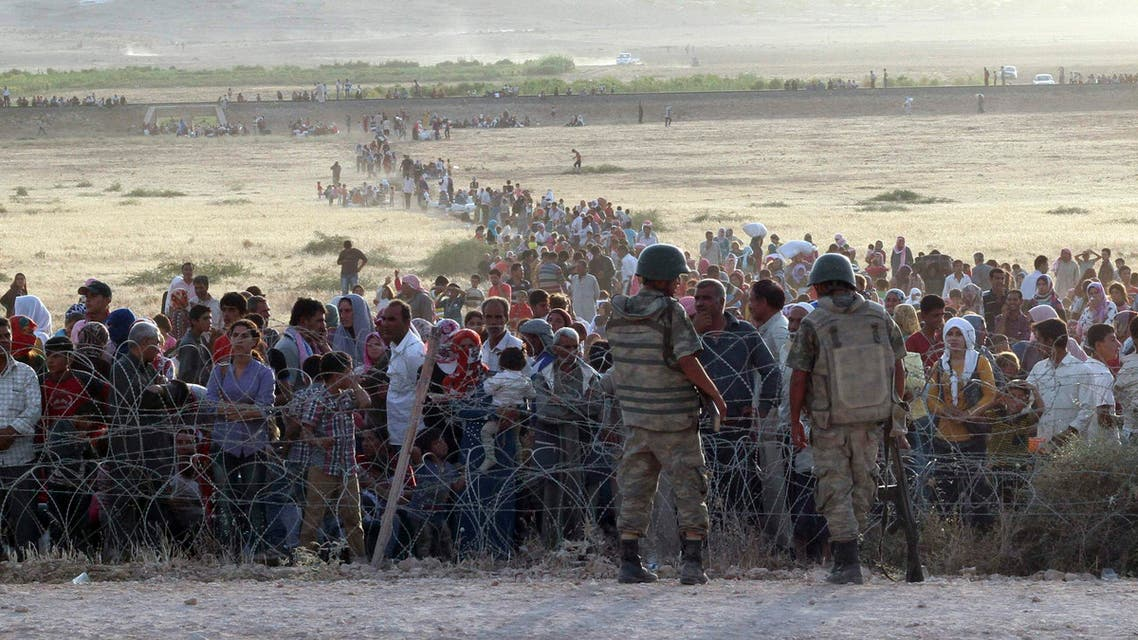 Turkish soldiers stand guard as Syrians wait behind the border fences near the southeastern town of Suruc in Sanliurfa province, September 18, 2014.  (Reuters)