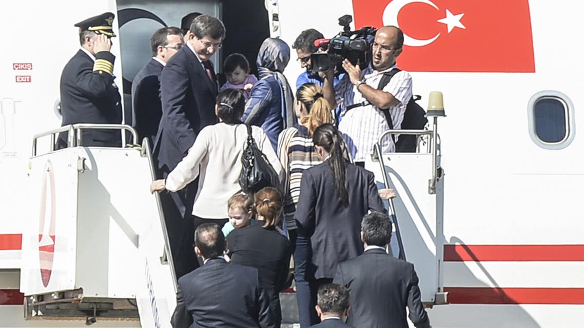 Turkish Prime Minister Ahmet Davutoglu (L) gets into his plane with freed hostages on September 20, 2014. (AFP)