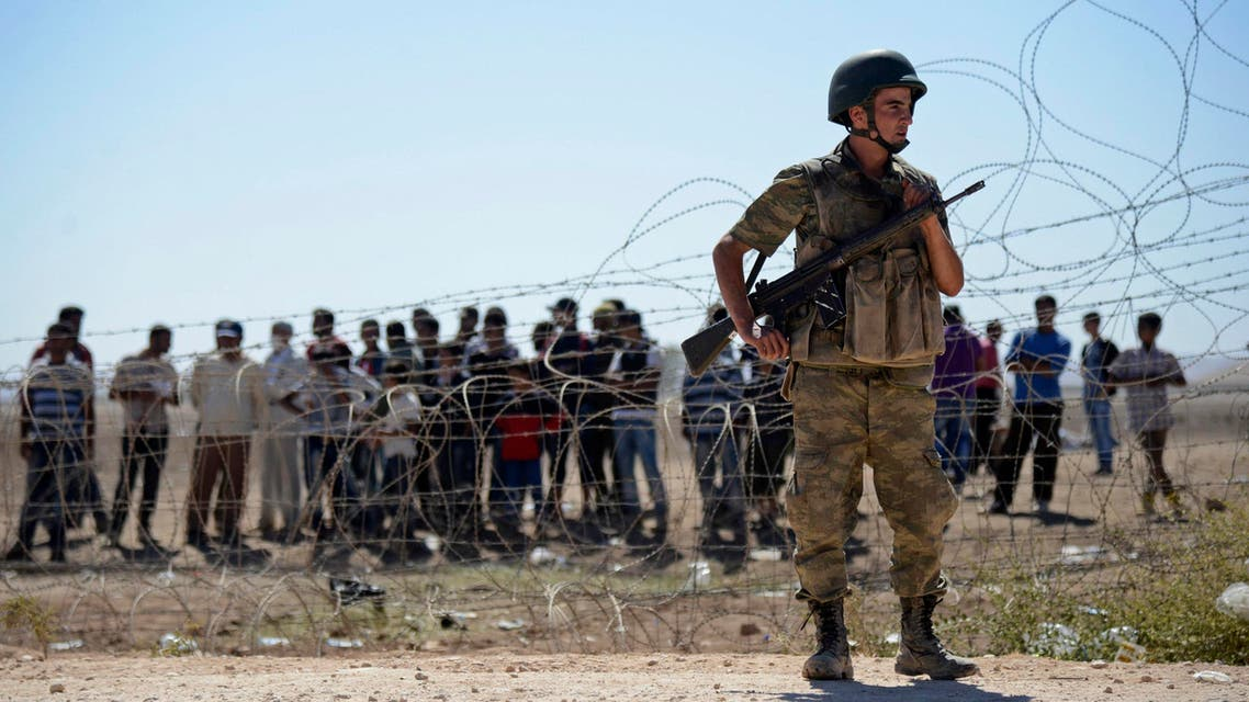 A Turkish soldier stands guard as Syrian Kurds wait behind the border fence near the southeastern town of Suruc in Sanliurfa province, September 21, 2014. (Reuters)