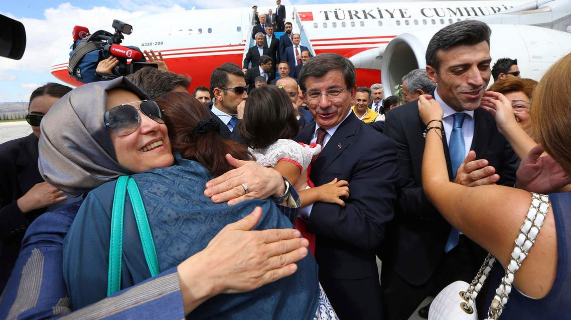 Turkish Consul General of Mosul Ozturk Yilmaz (2nd R) is welcomed by his relatives as Turkish Prime Minister Ahmet Davutoglu (C) looks on, as they arrive at Esenboga airport in Ankara September 20, 2014. (Reuters)