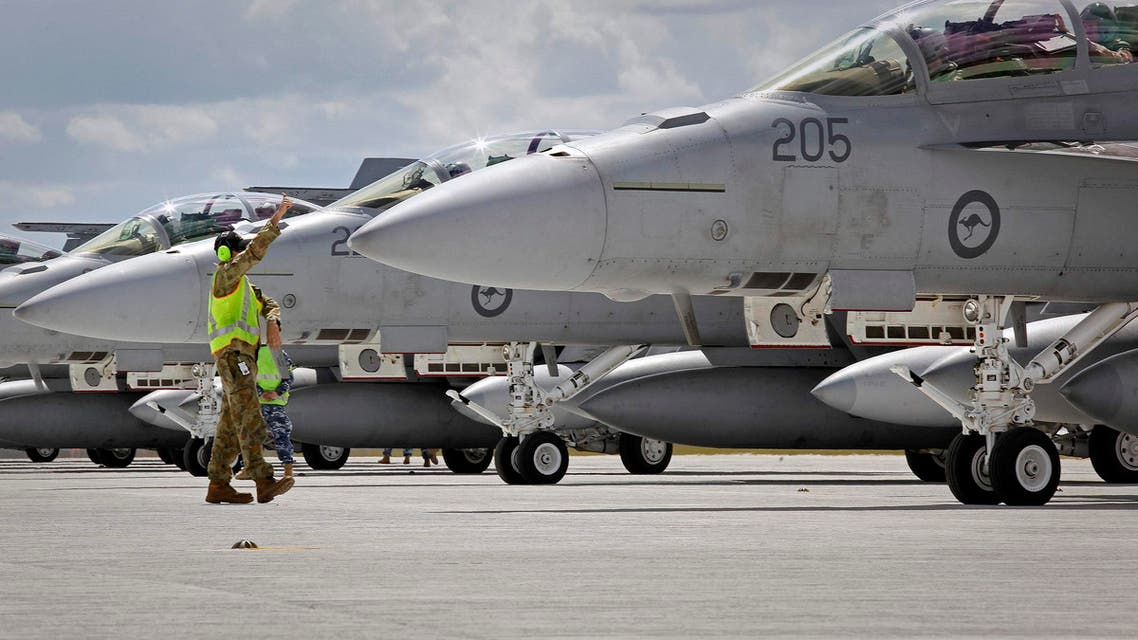 Ground staff assist crews of Royal Australian Air Force (RAAF) F/A-18F Super Hornets as they prepare to take-off from RAAF Base Amberley in Queensland in this handout picture taken on September 21, 2014 and released by the Australian Defence Force September 22, 2014. reuters