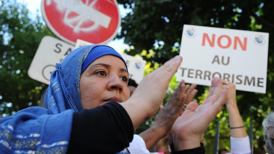 """eople hold a placard reading """"Terrorism, no"""" during a demonstration called by muslims groups to denounce the """"barbarism"""" of Islamic State militants, on Sept. 26, 2014 outside Paris's main mosque. (AFP)"""