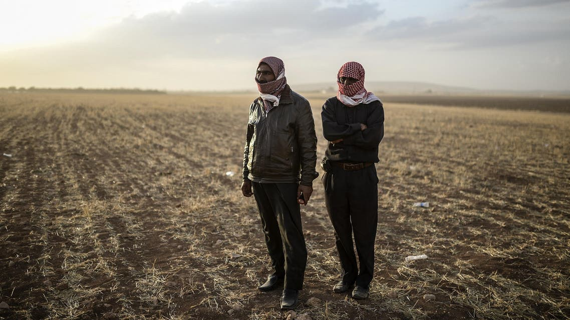 Syrian Kurdish men stand near the Syrian border at Suruc in Sanliurfa province, on Sept. 25, 2014. (AFP)